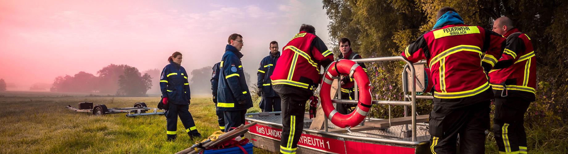 Startseiten Slider Katastrophenschutz - Feuerwehrleute auf einem Feld in der Dämmerung