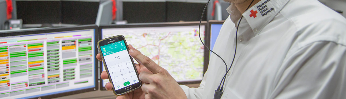 Mobilfunk-Ortung - Mann mit Handy vor Monitoren
