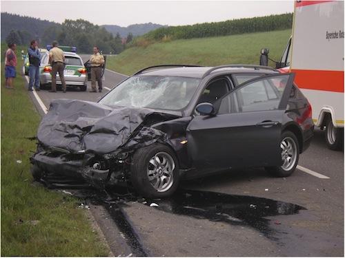 schwarzer PKW Unfallwagen auf einer Landstraße mit Polizei und Rettugnswagen
