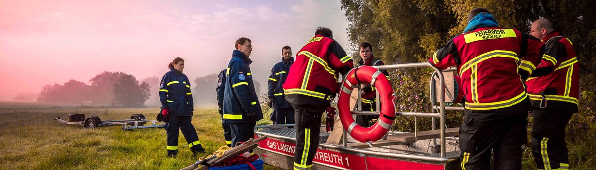 Feuerwehrleute auf einem Feld in der Dämmerung