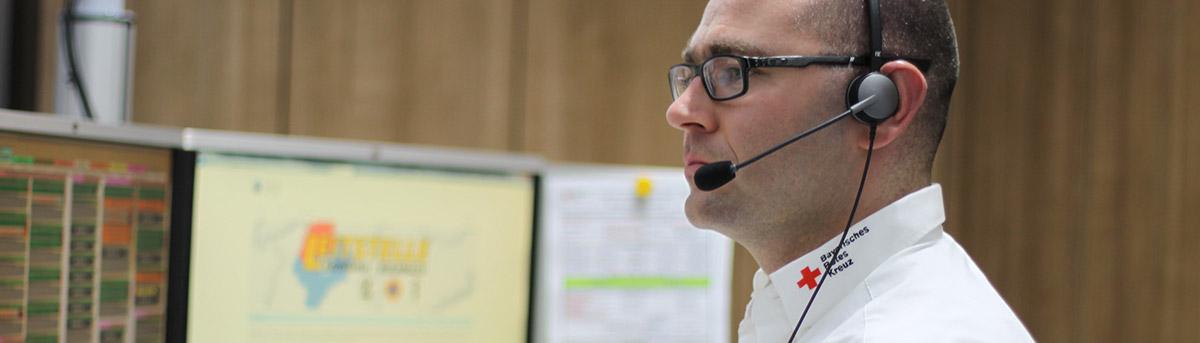 ILS-Mitarbeiter mit Headset vor Monitoren